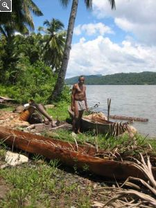 Papuan Man And Carved Trunk Canoes By Arguni Bay